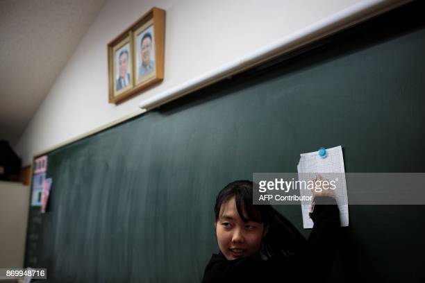 In this picture taken on October 13 a student looks at the results of an exam under portraits of late North Korean leaders Kim Il Sung and Kim Jong...