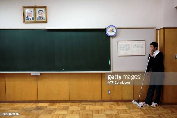 In this picture taken on October 13 a student pauses while cleaning the classroom under portraits of late North Korean leaders Kim Il Sung and Kim...