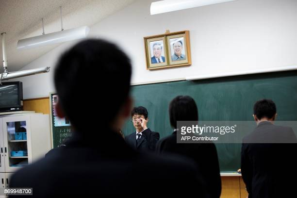 In this picture taken on October 13 a teacher gestures under portraits of late North Korean leaders Kim Il Sung and Kim Jong Il after giving an exam...