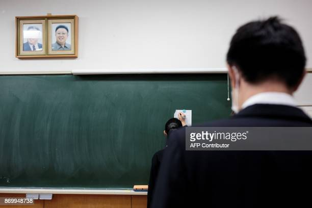In this picture taken on October 13 a teacher watches a student looking at the results of an exam under portraits of late North Korean leaders Kim Il...
