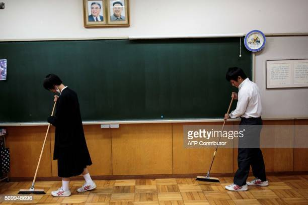 TOPSHOT In this picture taken on October 13 students clean the classroom under portraits of late North Korean leaders Kim Il Sung and Kim Jong Il...