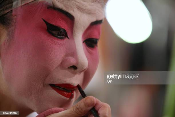 In this picture taken on October 15 a Chinese Cantonese opera singer applies makeup before performing during the Tin Hau festival in Hong Kong Tin...