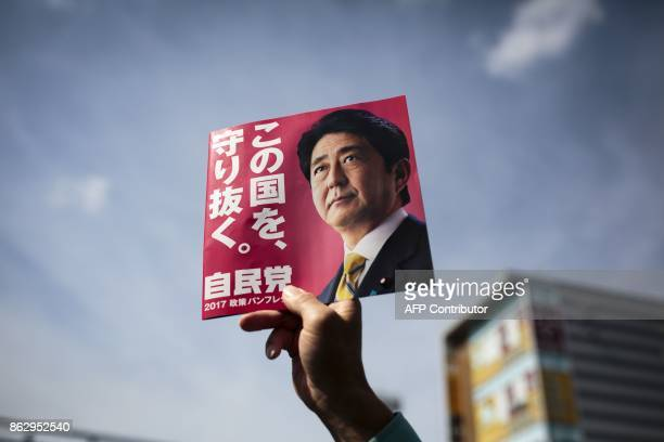 In this picture taken on October 18 a man holds an electoral leaflet of Japan's Prime Minister and ruling Liberal Democratic Party president Shinzo...