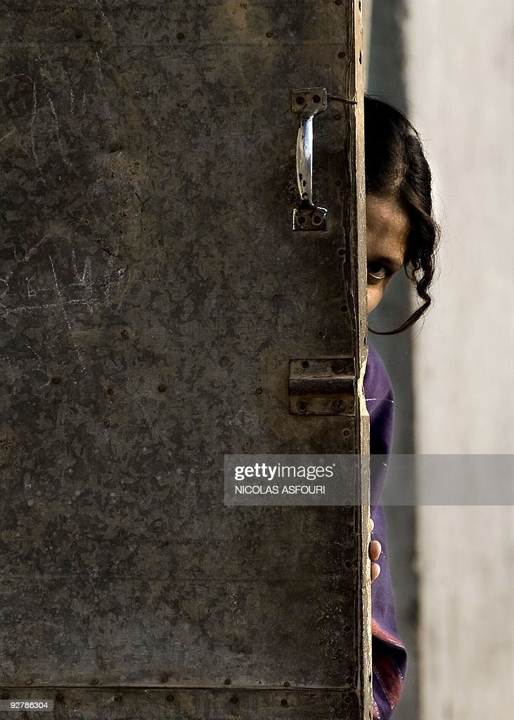 In this picture taken on October 18 a Pakistani girls peeks out of her house in Rawalpindi on the outskirts of capital Islamabad More than 100000...