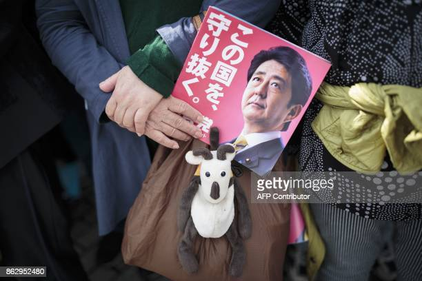 TOPSHOT In this picture taken on October 18 a woman holds an electoral leaflet of Japan's Prime Minister and ruling Liberal Democratic Party...