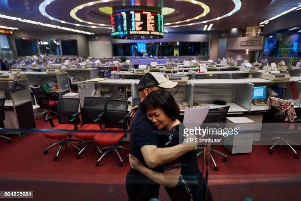 In this picture taken on October 19 Cheung a trader who has worked on the floor since 1994 hugs a colleague as she prepares to leave on her last day...