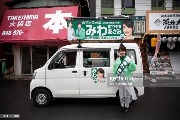 In this picture taken on October 20 Party of Hope candidate and former flight attendant Asami Miwa poses next to a campaign van decorated with a...