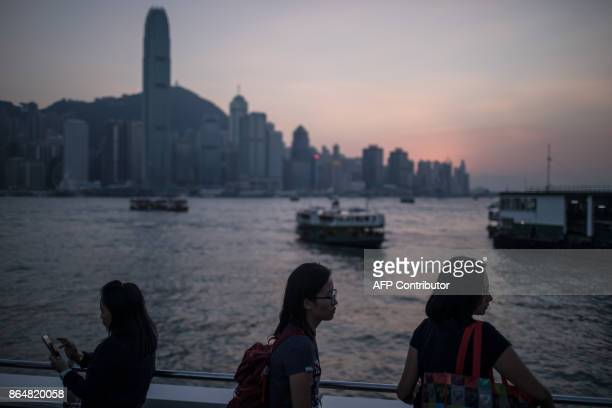 In this picture taken on October 21 tourists visit a promenade in front of the city skyline in Hong Kong / AFP PHOTO / DALE DE LA REY
