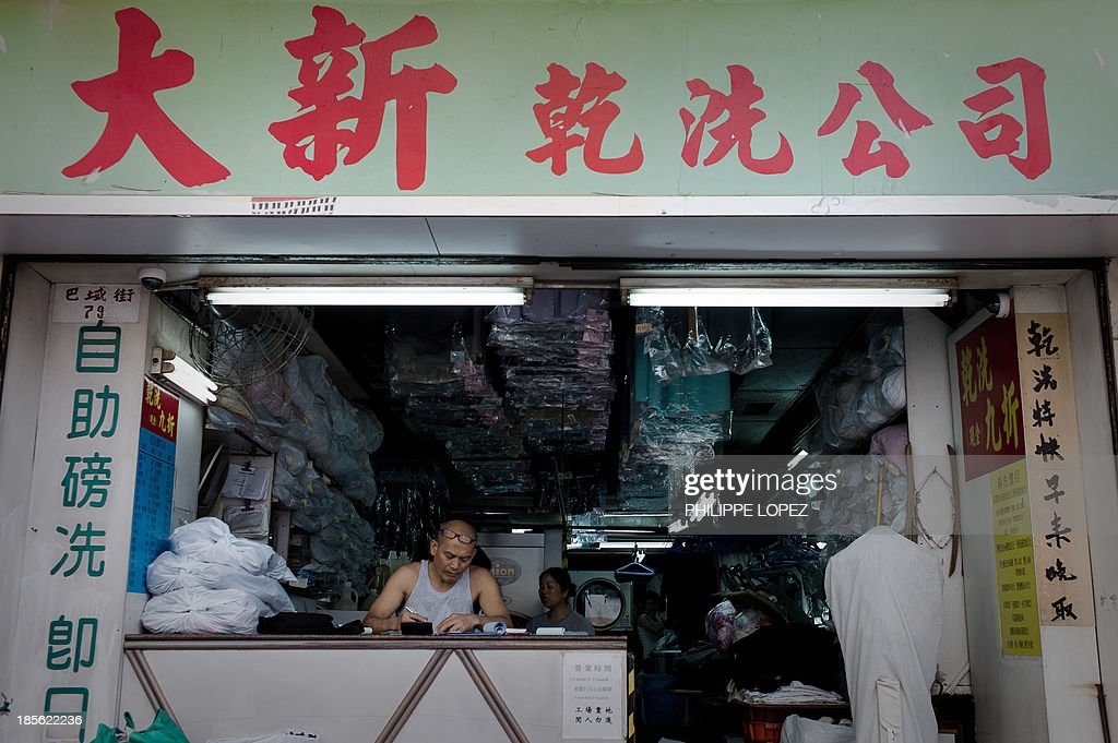 In this picture taken on October 22, 2013 in Hong Kong, a man stands at the counter of a laundry shop in the Sham Shui Po district, where a public resettlement block built in 1954 was renovated and turned into a youth hostel. While heritage regularly falls victim to construction in one of the most densely populated cities in the world, the building was preserved as a record of Hong Kong's public housing development. The museum takes visitors through the history of Sham Shui Po, the district where the building has stood for half a century. AFP PHOTO / Philippe Lopez