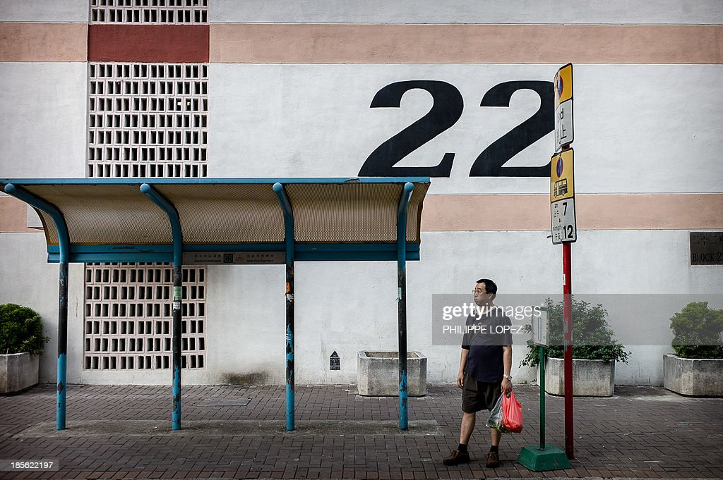 In this picture taken on October 22, 2013 in Hong Kong, a man waits at a bus stop in front of buildings of the Sham Shui Po district, where a public resettlement block built in 1954 was renovated and turned into a youth hostel. While heritage regularly falls victim to construction in one of the most densely populated cities in the world, the building was preserved as a record of Hong Kong's public housing development. With a museum set up in the hostel itself, visitors are taken through the history of Sham Shui Po, the district where the building has stood for half a century. AFP PHOTO / Philippe Lopez