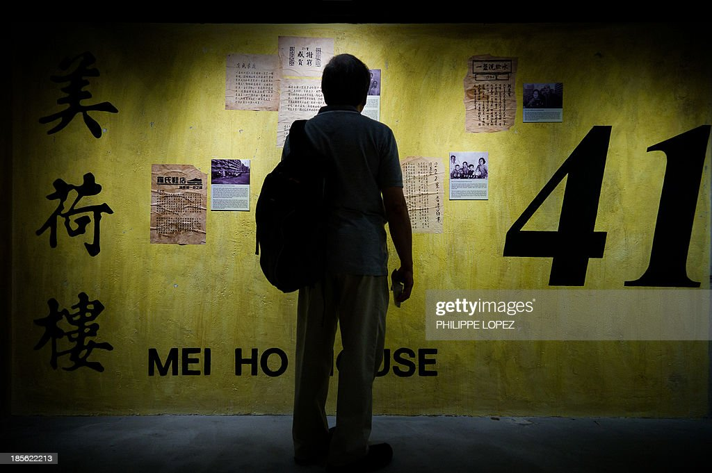 In this picture taken on October 22, 2013 in Hong Kong, a visitor reads informations of past residents on a wall marked with a block number in reference of the way early public housing building were marked, at the museum of the Mei Ho House, a public resettlement block built in 1954 and renovated to be turned into a youth hostel. While heritage regularly falls victim to construction in one of the most densely populated cities in the world, the building was preserved as a record of Hong Kong's public housing development. The museum takes visitors through the history of Sham Shui Po, the district where the building has stood for half a century. AFP PHOTO / Philippe Lopez