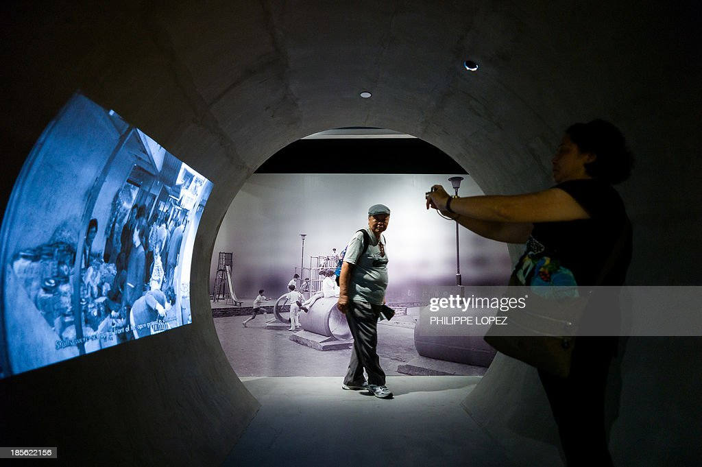 In this picture taken on October 22, 2013 in Hong Kong, a visitor takes pictures at the museum of the Mei Ho House, a public resettlement block built in 1954 and renovated to be turned into a youth hostel. While heritage regularly falls victim to construction in one of the most densely populated cities in the world, the building was preserved as a record of Hong Kong's public housing development. The museum takes visitors through the history of Sham Shui Po, the district where the building has stood for half a century. AFP PHOTO / Philippe Lopez