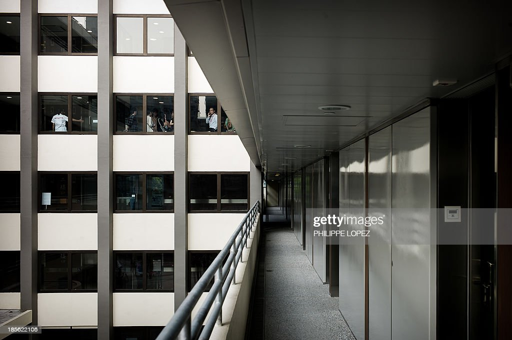 In this picture taken on October 22, 2013 in Hong Kong, visitors are seen at the windows of the renovated Mei Ho House, a public resettlement block built in 1954 and renovated to be turned into a youth hostel. While heritage regularly falls victim to construction in one of the most densely populated cities in the world, the building was preserved as a record of Hong Kong's public housing development. With a museum set up in the hostel itself, visitors are taken through the history of Sham Shui Po, the district where the building has stood for half a century. AFP PHOTO / Philippe Lopez