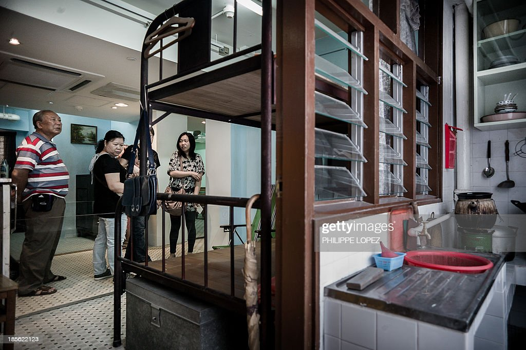 In this picture taken on October 22, 2013 in Hong Kong, visitors take pictures of re-created living space of early public housing estates at the museum of the Mei Ho House, a public resettlement block built in 1954 and renovated to be turned into a youth hostel. While heritage regularly falls victim to construction in one of the most densely populated cities in the world, the building was preserved as a record of Hong Kong's public housing development. The museum takes visitors through the history of Sham Shui Po, the district where the building has stood for half a century. AFP PHOTO / Philippe Lopez