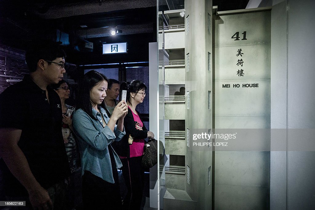 In this picture taken on October 22, 2013 in Hong Kong, visitors take pictures of a model of the Mei Ho House, a public resettlement block built in 1954 and renovated to be turned into a youth hostel. While heritage regularly falls victim to construction in one of the most densely populated cities in the world, the building was preserved as a record of Hong Kong's public housing development. The museum takes visitors through the history of Sham Shui Po, the district where the building has stood for half a century. AFP PHOTO / Philippe Lopez