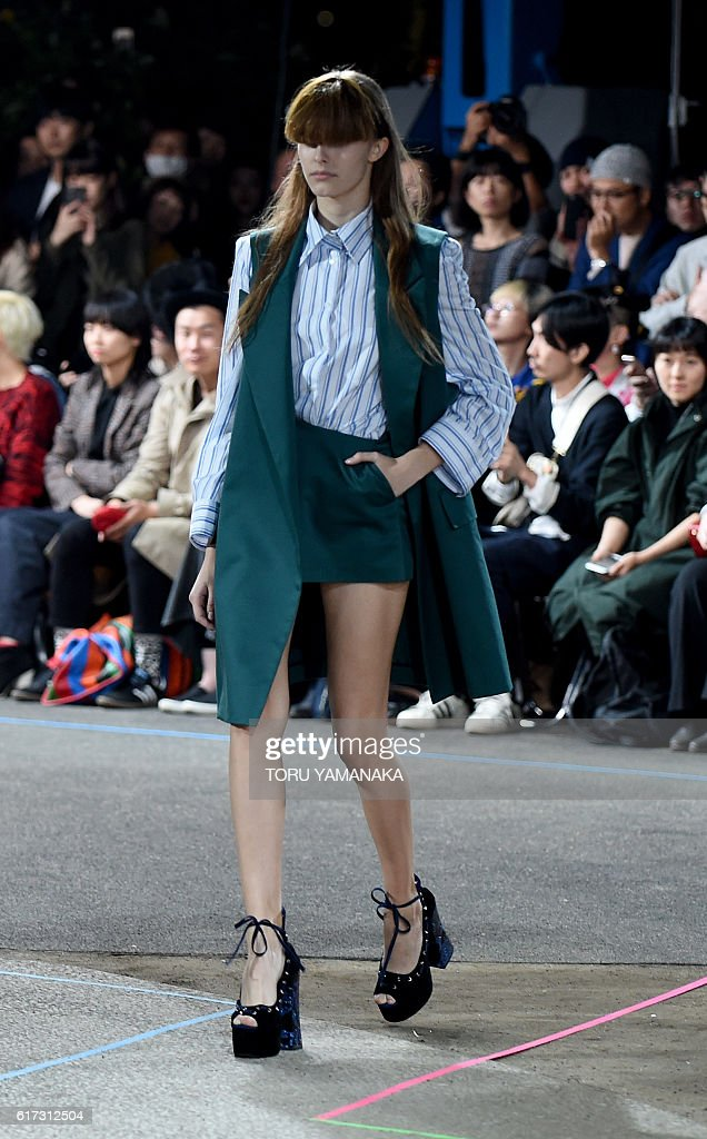In this picture taken on October 22, 2016, a model presents a creation of MIKIO SAKABE designed by Mikio Sakabe and Shueh Jen-Fang during the 2017 Spring/Summer Collection show at Tokyo Fashion Week. The Marc Jacobs of Japan, singing cats and models cloaked into armour: J-pop and science fiction transformed Tokyo Fashion Week spring/summer 2017 into a style fest unlike any other. / AFP / TORU