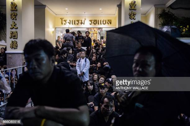 TOPSHOT In this picture taken on October 24 mourners shelter from the rain with umbrellas and plastic ponchos as they gather at night while waiting...