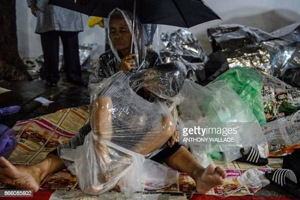In this picture taken on October 24 mourners shelter from the rain with umbrellas and plastic ponchos as they gather at night while waiting for the...