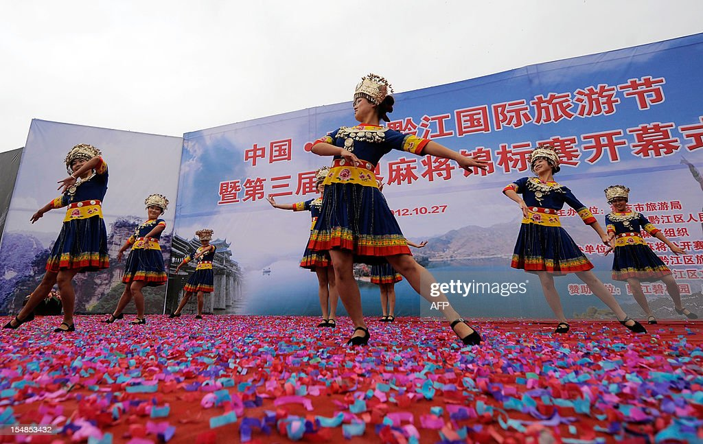 In this picture taken on October 27, 2012 Chinese hostesses in tribal costumes perform at the opening ceremony of the 3rd Mahjong World Championship in Chongqing. Some 118 participants are taking part in the three-day competition for the title of the best Mahjong player in the world. CHINA