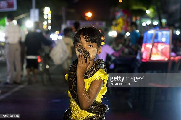 In this picture taken on October 6 a girl kisses a snake during the Thadingyut full moon day festival in Yangon The lighting festival is celebrated...