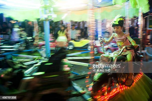 In this picture taken on October 6 a girl plays on a fun ride during the Thadingyut full moon day festival in Yangon The lighting festival is...