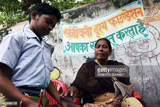 HARRIS In this picture taken on September 2 Indian teacher Rangamma Kaul who runs an art school instructs student Ashish Gupta at the school in...
