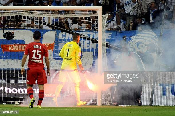 In this picture taken on September 20 2015 Lyon's FrenchPortuguese goalkeeper Anthony Lopes holds a smoke flare thrown onto the pitch during the...