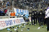In this picture taken on September 20 2015 riot police patrol around the touchline after crowd trouble during the French L1 football match Marseille...