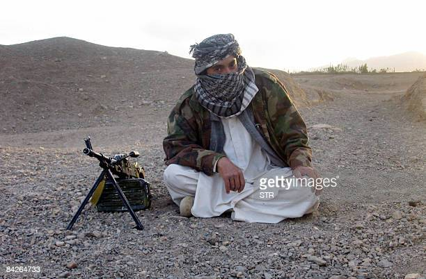 In this picture taken on September 26 a fighter with Afghanistan's Taliban militia poses with a machine gun on a hillside at Maydan Shahr in Wardak...