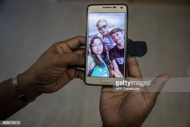 In this picture taken on September 3 Analyn Tapil a member of the 'Unsung Heroes' choir and Filipina domestic worker shows a photograph with her two...