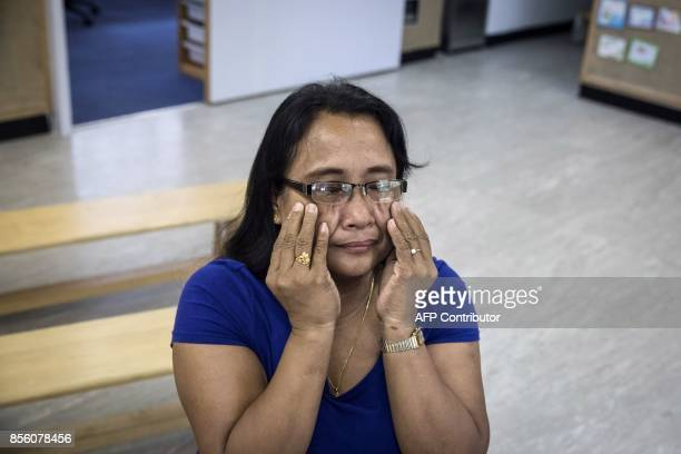 In this picture taken on September 3 Analyn Tapil a member of the 'Unsung Heroes' choir and Filipina domestic worker reacts while speaking about her...