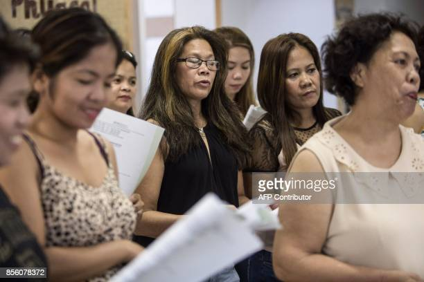 In this picture taken on September 3 Filipina domestic workers who are members of the 'Unsung Heroes' choir take part in a practice session inside a...