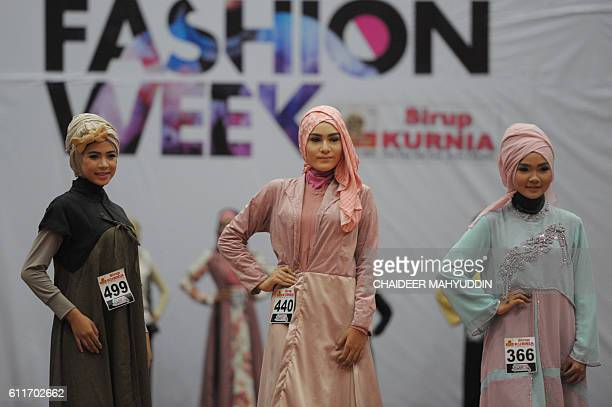 In this picture taken on September 30 models in modern hijab parade on the catwalk during Aceh Fashion Week in Banda Aceh / AFP / CHAIDEER MAHYUDDIN