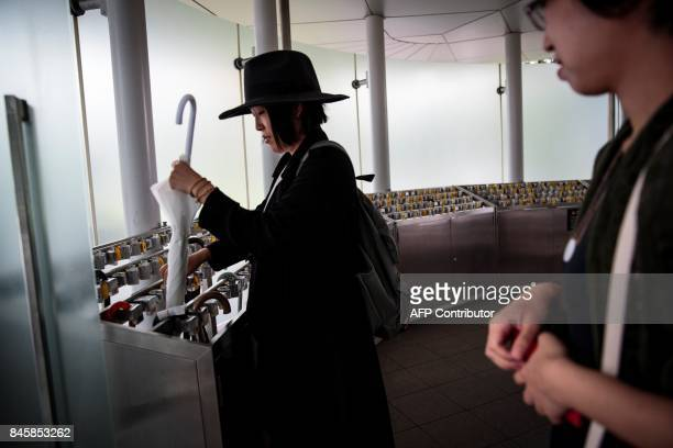 In this picture taken on September 4 a Japanese woman takes her umbrella at an umbrella lockup in Tokyo's National Art Center Heated toilets that...