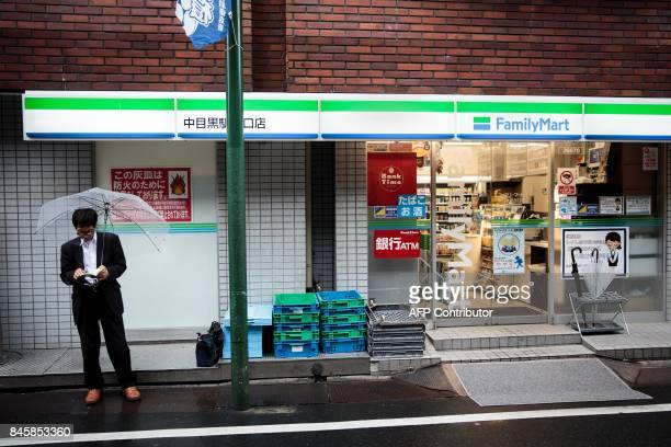 In this picture taken on September 4 a man reads a book as he smokes next to a convenience store in the Nakameguro district in Tokyo Heated toilets...