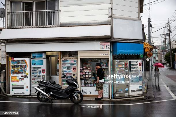 In this picture taken on September 4 a man smokes a cigarette next to vending machines in the Nakameguro district of Tokyo Heated toilets that spray...