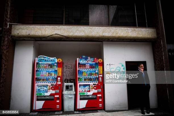 In this picture taken on September 4 a man speaks on his phone next to drink vending machines in the Roppongi district in Tokyo Heated toilets that...