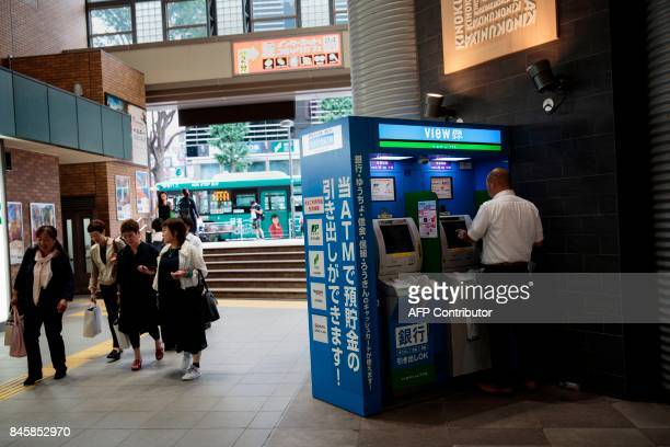 In this picture taken on September 4 a man uses an ATM at Ebisu subway station in Tokyo Heated toilets that spray users clean train seats that...