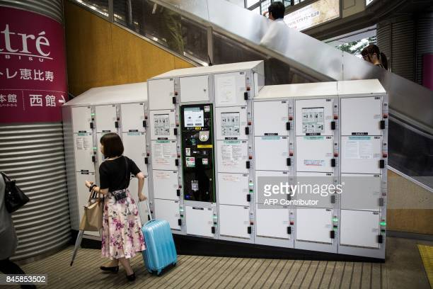 In this picture taken on September 4 a woman pulls her suitcase after taking it from a locker at Ebisu subway station in Tokyo Heated toilets that...