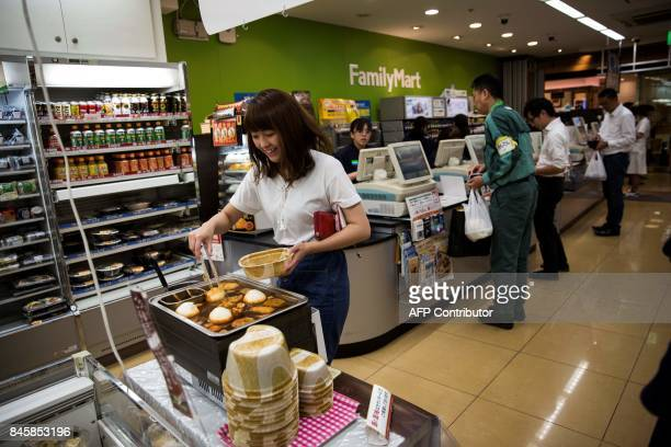 In this picture taken on September 4 a woman servers herself some hot food at a convenience store in the Roppongi district in Tokyo Heated toilets...