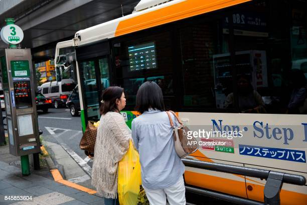 In this picture taken on September 4 passengers stand next to a bus which works with subway electronic transport cards of 'pasmo' and 'Suica' at a...