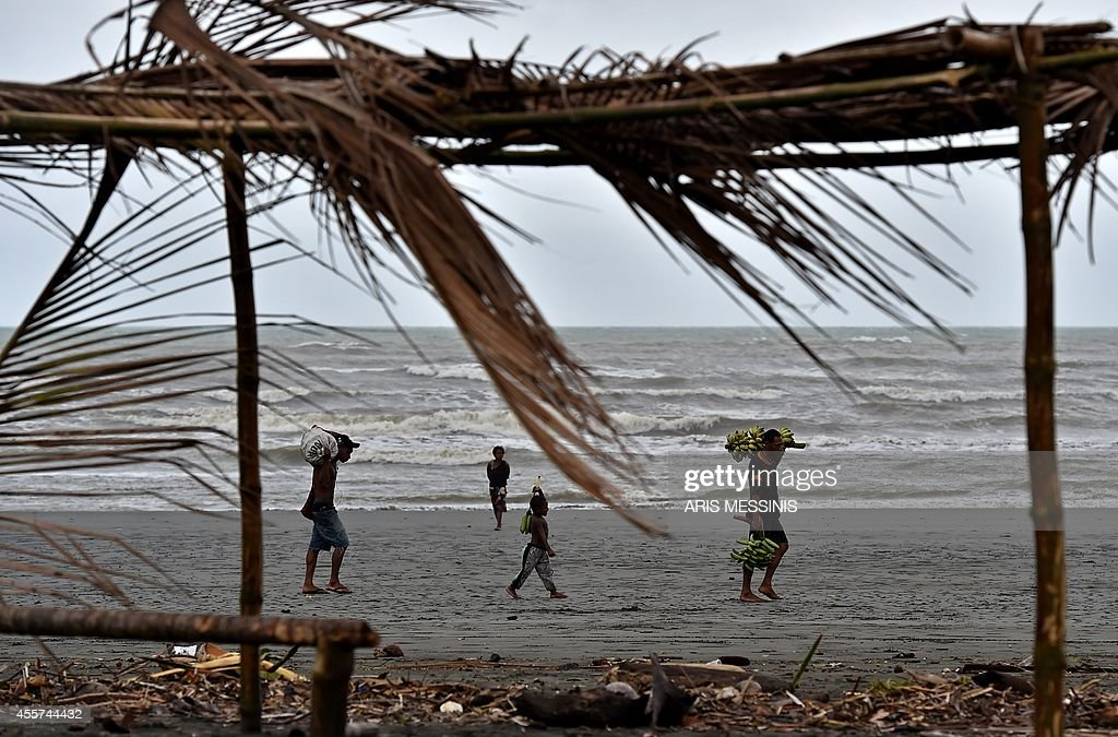 In this picture taken on September 7 a family carry food supplies at the beach of Kerema AFP PHOTO / ARIS MESSINIS