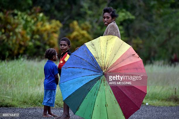 In this picture taken on September 7 woman and her child look on as they stand behind an umbrella in the town of Kerema AFP PHOTO / ARIS MESSINIS