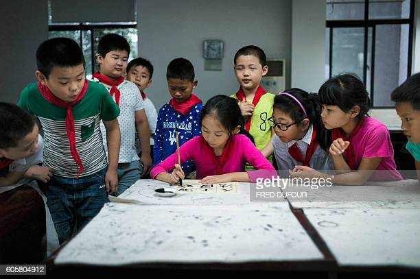 In this picture taken on September 8 a young girl writes Chinese characters at an elementary school in Zhujiajiao on the outskirts of Shanghai / AFP...
