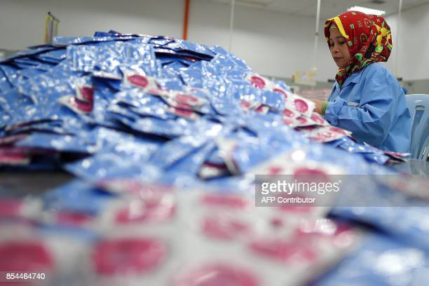 TOPSHOT In this picture taken September 20 a worker packs condoms at the Malaysian condommaker Karex Industries headquarters in Port Klang After...