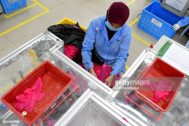 In this picture taken September 20 a worker tests condoms at the Malaysian condommaker Karex Industries headquarters in Port Klang After enjoying...