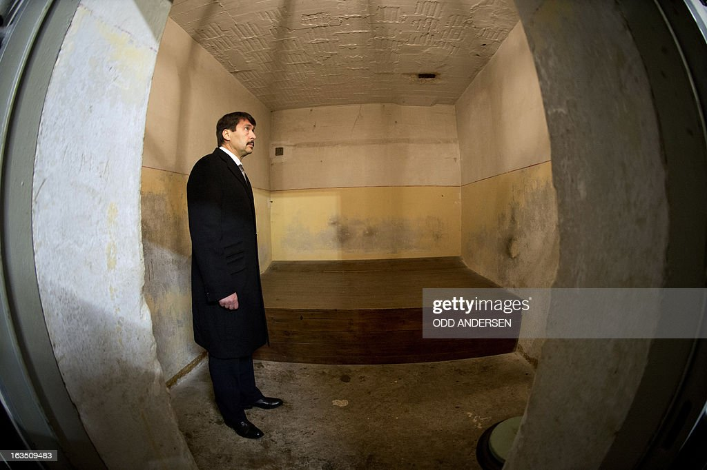 In this picture taken with a fisheye lens Hungarian President Janos Ader stands inside a bunker cell of the former East German secret police (STASI) prison in Hohenschoenhausen, Berlin on March 11, 2013. Ader is on a state visit to Germany . The prison is a memorial site since 1994.