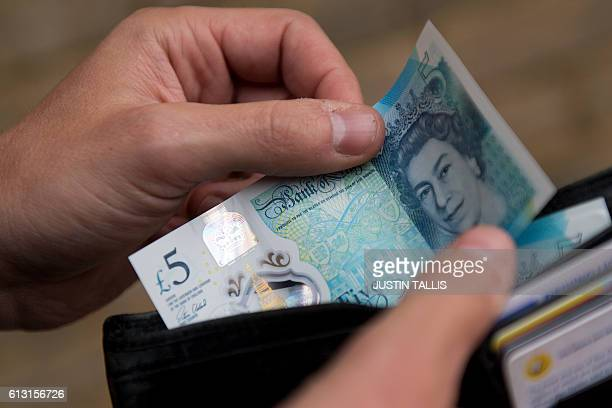 In this posed photograph a person is pictured holding a wallet containing a £5 note in London on October 7 2016 The Bank of England is 'looking into'...