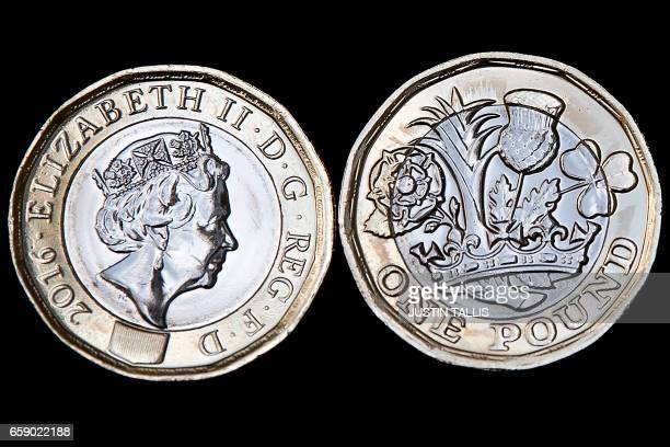 In this posed photograph the obverse and reverse of a newly issued 12sided £1 coin is pictured in London on March 28 2017 Britain's new £1 coin with...