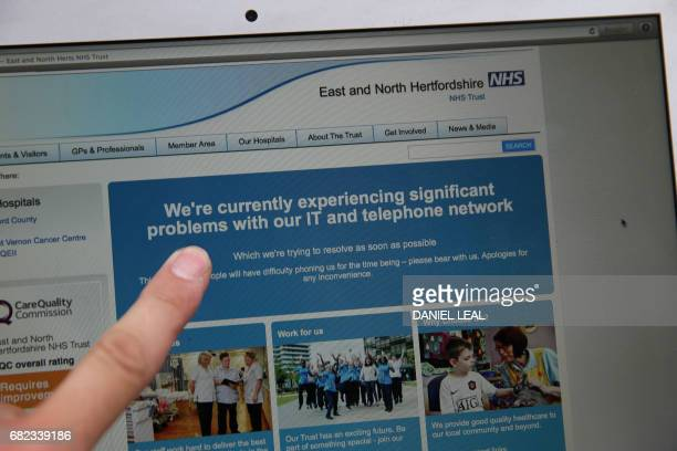 In this posed picture photograph a woman points to the website of the NHS East and North Hertfordshire notifying users of a problem in its network in...